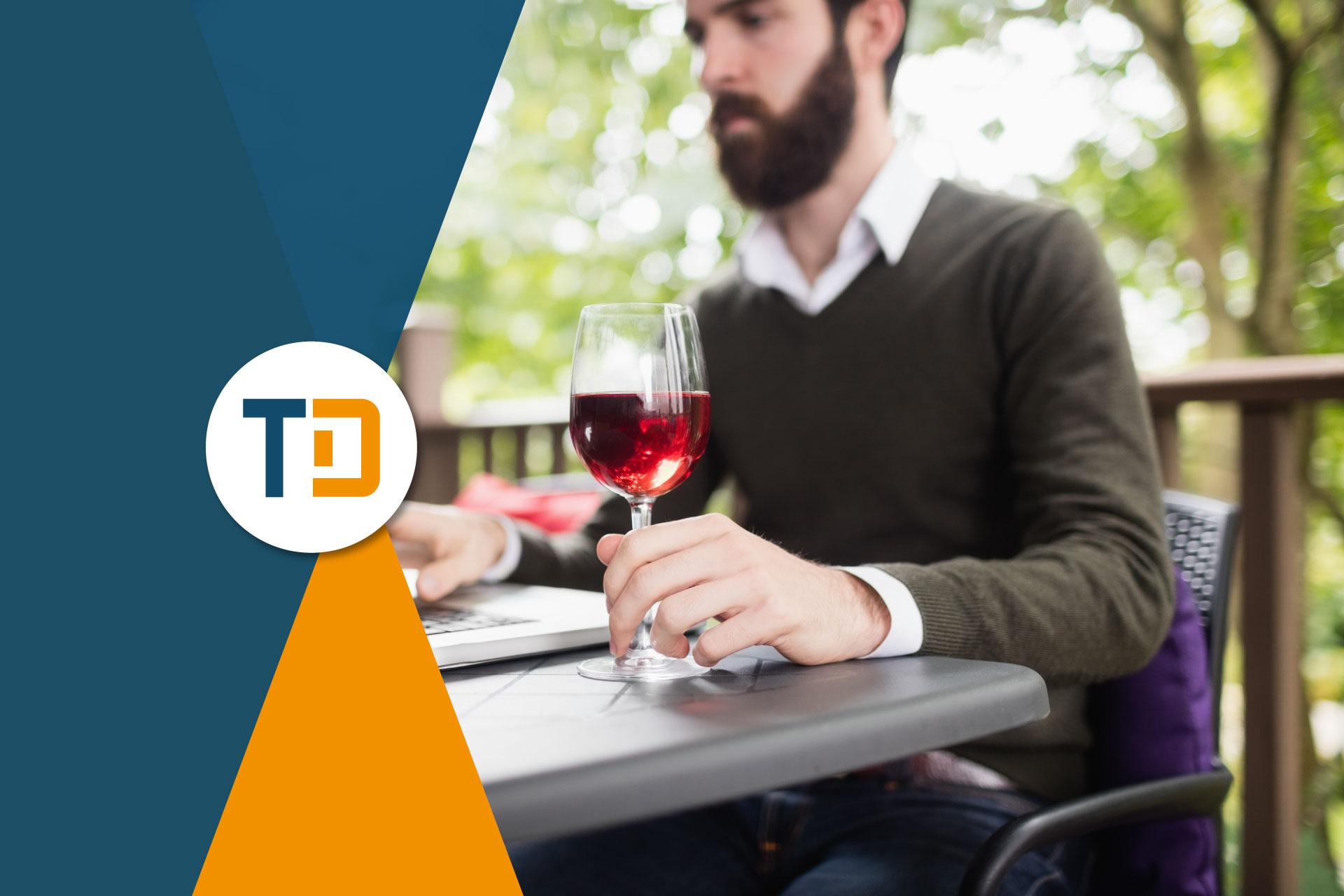 Uomo tiene in mano un bicchiere di vino rosso mentre utilizza il computer